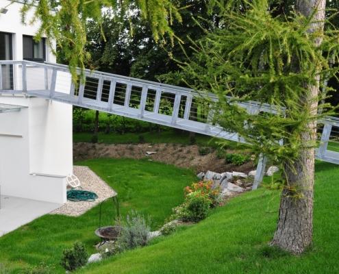 Gartensteg verzinkt mit Trittflächen aus Gitterrosten und Geländer mit Edelstahlseilen