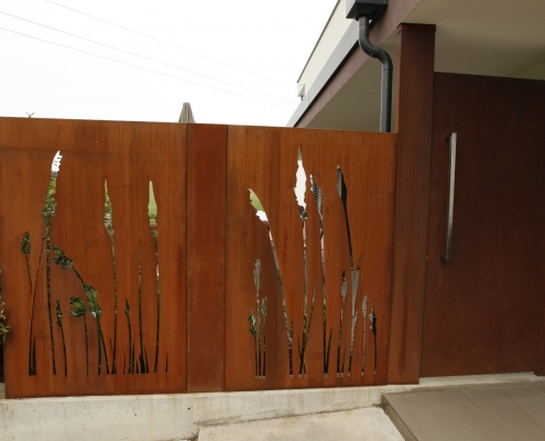 Sichtschutz mit Lasermotiv und Eingangstür aus Cortenstahl
